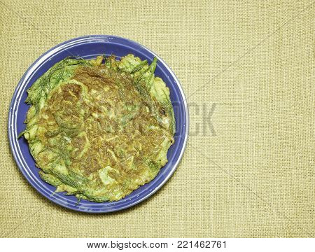 Thai-style omelette with herb on dish Hessian sackcloth woven background,consist of eggs,Climbing wattle(CHA-OM)
