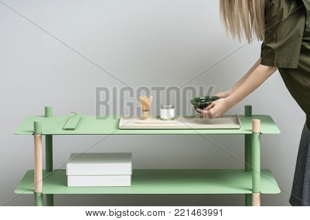 Blonde girl holds an emerald bowl over the green metallic-wooden stand on the gray wall background in the studio. On the stand there is white box, colorful metal supports, jar, tea whisk. Horizontal.