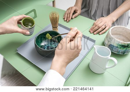 People preparing a chinese matcha green tea on the green metal table indoors. One woman measures tea powder with a wooden stick over the bowl. On the table there is tea whisk and white jug with water.