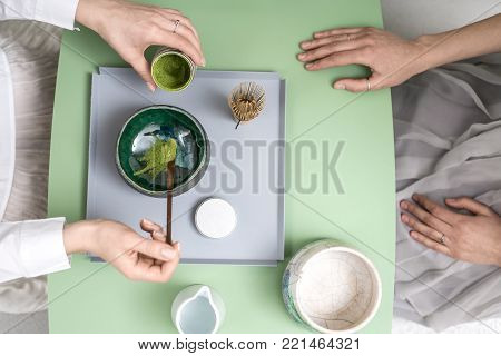 Two girls preparing a chinese matcha green tea on the green metal table indoors. One woman puts tea powder into the colorful bowl. On the table there is a wooden tea whisk and white jug with water.