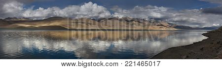 Mountain lake, photo panorama: hills and peaks on the shore of blue calm water, mirror-topped peaks, rosy white clouds in blue sky, Tibet, Himalayas.