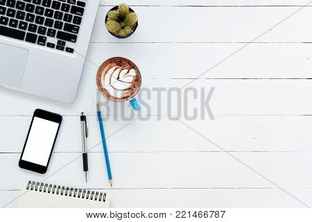 Office desk table with laptop,smart phone,cup of coffee,pen,pencil and notebook.Flat lay photo.Top view with copy space.Office supplies and gadgets on desk table.Working desk table concept.