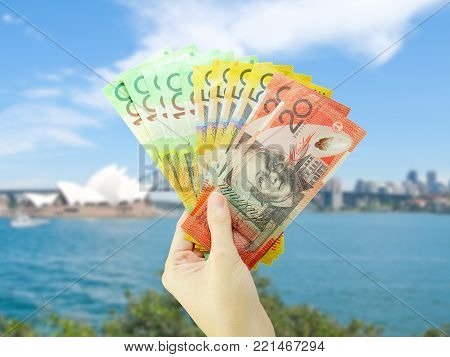 Hand holding Australian money on Sydney cityscape background. Business and finance concept.