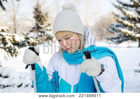 attractive blonde girl with ski sticks in her hands wearily stands in winter forest, relaxing during skiing trip