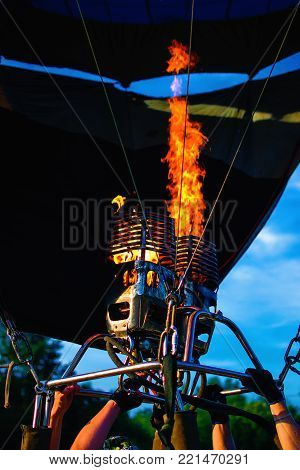 Hot air balloon is inflated for flight by a torch with a bright powerful flame.