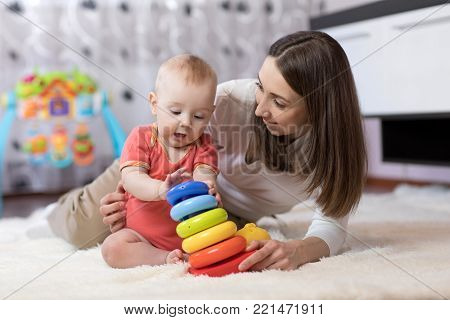 little baby boy and his mommy play with toys at home