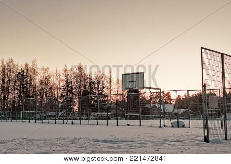 The town basketball field is covered with heavy snow at the rural town of Oulainen, Finland. The sun is setting early in this midwinter day.