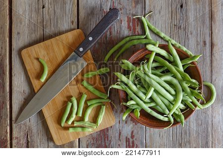 Healthy food. String beans, raw asparagus in a clay bowl closeup.top view on the wooden background