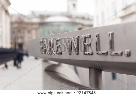 Farewell word written with metal letters in London with blurred background