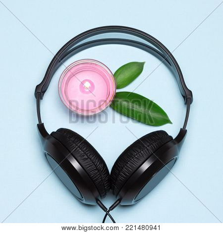 Headphones and burning candle with green leaves. Relaxing music with nature sounds concept