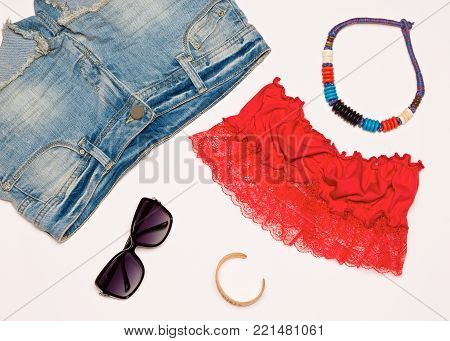 Fashion summer outfit. Denim shorts, bright red bandeau top, necklace, bracelet and sunglasses. Trendy women clothing and accessories