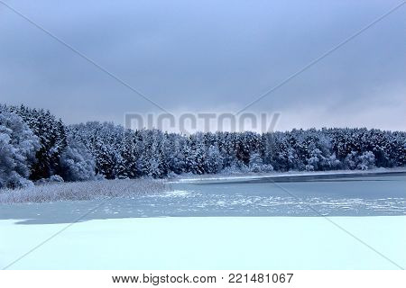 Winter forest and lake. Northern nature.Trees in the winter. The snow on the trees. The snow on the branches. Christmas mood. Winter lake. The ice on the lake. The water was cold. The river in winter. The ice on the water. Beautiful winter landscape
