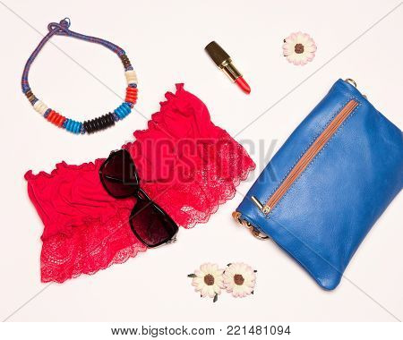 Fashion women accessories for summer walk. Bright bandeau top, necklace, pouch, red lipstick and sunglasses