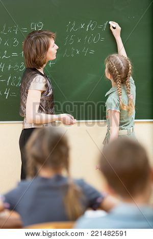 School children with teacher in classroom. Pupil solving task and writing on blackboard.