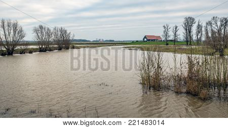 Panoramic image of a Dutch polder flooded by the high water level in the nearby river. In the background is a new farm, built on a mound.