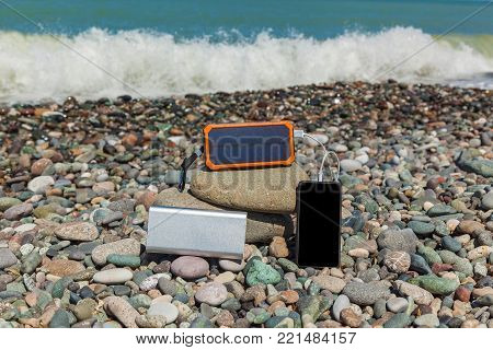 the poverbank lies on the pebbles by the sea and charges the phone. Powerbank charges the phone.