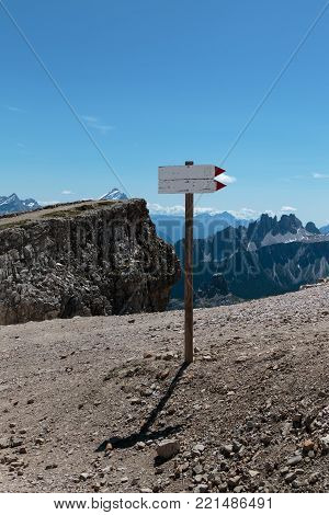 Wooden Direction Path Sign in Barren Rocky Mountain.