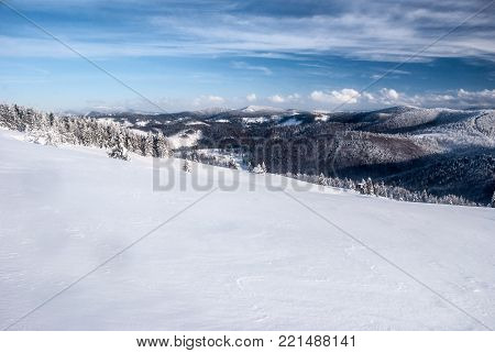 Hala na Malej Raczy mountain meadow with snow,  isolated house, forest around, hills on the background and blue sky with clouds in winter Beskid Zywiecki mountains in Poland