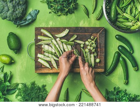 Healthy green vegan cooking ingredients. Flay-lay of female hands cutting green vegetables and greens over green background, top view. Clean eating, vegetarian, detox, dieting food concept