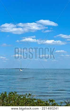 the yacht with masts lonely swims, a lone yacht on the horizon