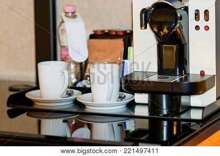 two white cups and cofee machine on table