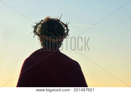 Jesus Christ with crown of thorns against the sun