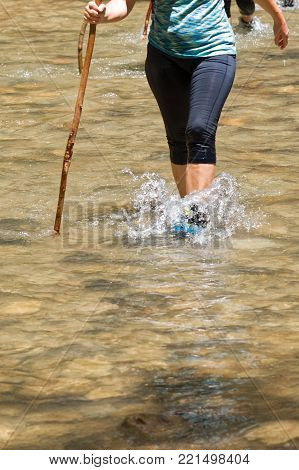 Female hiker walking in a creek using a support. Dressed with leggings. Detail of the river.