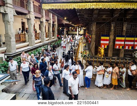 Kandy, Sri Lanka - November 8, 2017: Sri Lankan Buddhists queueing  up at the Temple of Sacred Tooth  Relic for paying respect to the Buddha tooth relic while the group of tourists walking past.