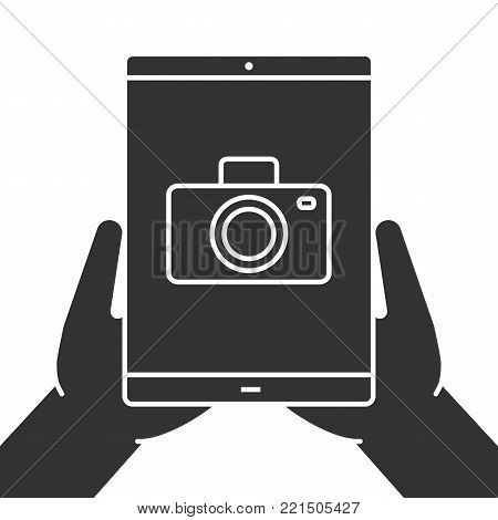Hands holding tablet computer glyph icon. Photos view. Silhouette symbol. Tablet computer with camera. Negative space. Vector isolated illustration