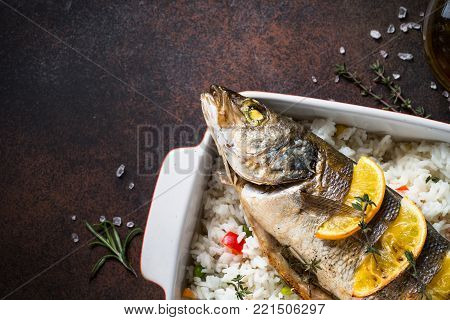 Fish seabass baked with rice and vegetables. Top view with copy space.