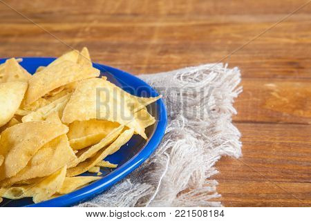Nachos corn chips in blue plate on sackcloth on wooden table