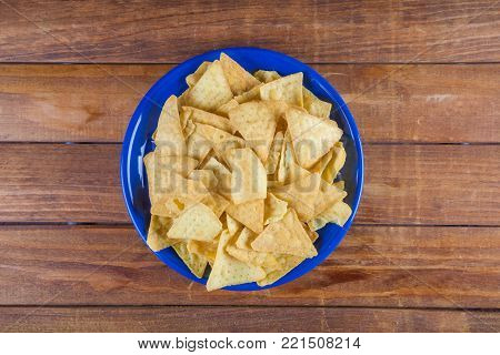 Nachos corn chips in blue plate on wooden table. Top view