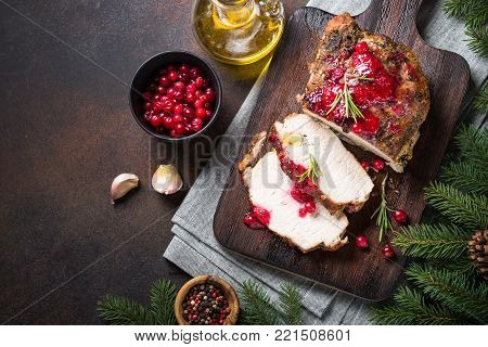 Baked pork meat with cranberry sauce. Christmas food. Winter meat recipe. Top view with copy space on dark stone table.