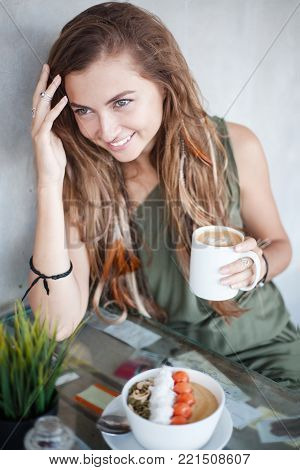 Beautiful smiling girl with long hair with pigtails and feathers is sitting in a cafe. She is looking away and holds a mug of coffee. A muesli bowl is on the table in front of her.