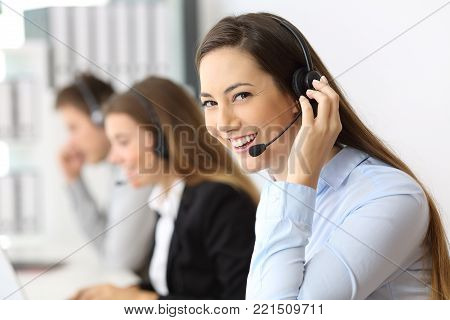Portrait of a happy telemarketer working looking at you at call center