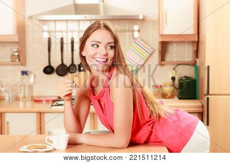 Happy woman with tea or coffee eating heart shape gingerbread cookie. Pretty gorgeous young girl with hot beverage relaxing in kitchen.