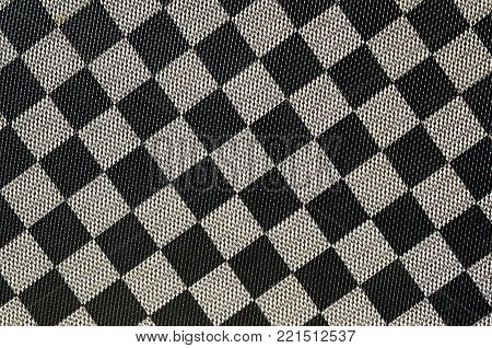 Plastic texture in the form of a very small cloth binding, painted in black and gray in the style of a chessboard. Macro shot
