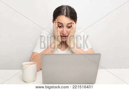 Young woman staring at a laptop in disbelief and shock resting her face on her hands as she stares at the screen