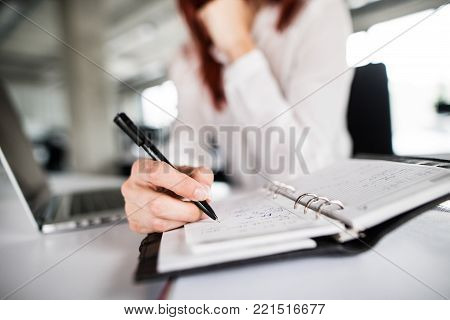 Unrecognizable businesswoman in the office, sitting at the desk, writing something into her personal organizer. Close up.
