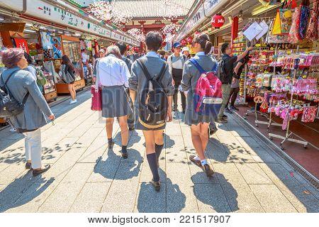 Tokyo, Japan - April 19, 2017: people in school uniforms walking on Nakamise Dori, street with food and souvenirs shops. Kaminarimon Gate of Senso-ji Buddhist Temple, Asakusa, on background.