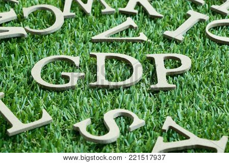 Wood letter in word GDP (Abbreviation from Good distribution practice or Gross domestic product) on artificial green grass wit English alphabet background