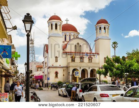 Rethymno, Greece - May 3, 2016: Touristic attraction Eastern Orthodox Church Of Four Witnesses. Tourists walk the streets of old town. Mediterranean architecture on Crete, Rethymno, Greece