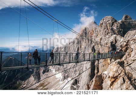 Ramsau am Dachstein, Austria - October 2, 2017: Tourists walk on suspension rope bridge Sky Walk in Dachstein Mountain