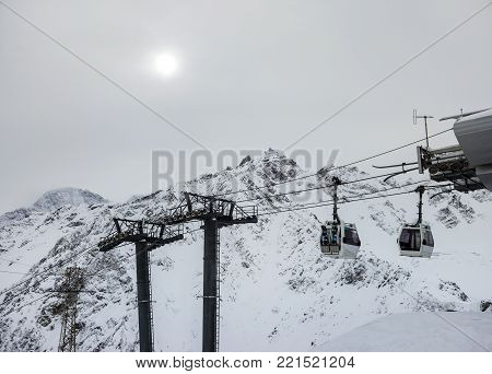 Cableway in motion on rise and descent on ski resort on background beautiful landscape of snowy high mountains Caucasus Elbrus