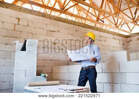 Senior architect or civil engineer at the construction site looking at blueprints, controlling issues at the construction site.
