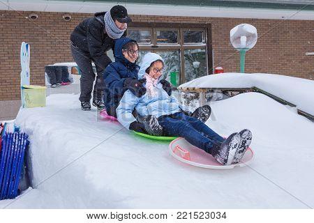 Hokkaido, Japan - 28 December 2017 - Asian teenagers have fun sliding down on snow slope on plastic snow slide discs in Hokkaido, Japan on December 28, 2017