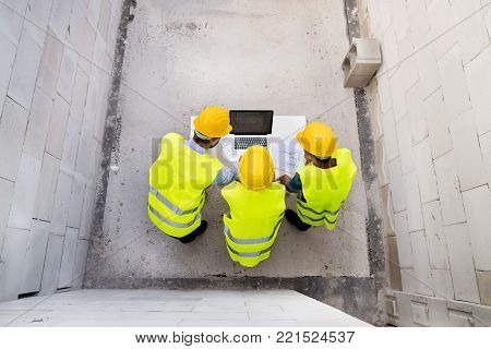 Architect, civil engineer and worker looking at plans and blueprints, discussing issues at the construction site.