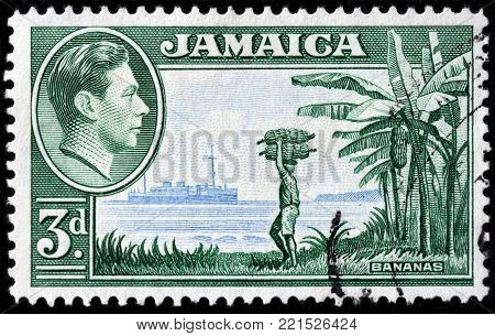 LUGA, RUSSIA - OCTOBER 7, 2017: A stamp printed by JAMAICA shows image portrait of  King George VI against banana tree and man carrying bunch of bananas, circa 1938