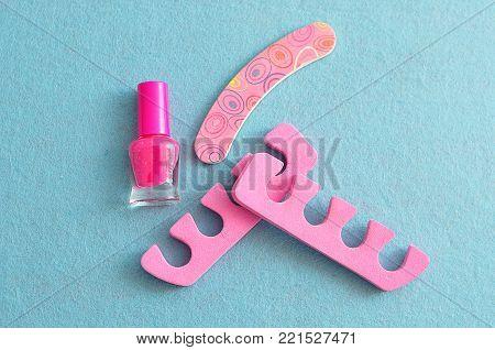 Pink nail polish with pink toe dividers and a pink nail file