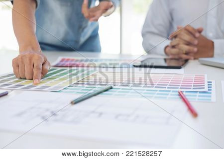Two interior design or graphic designer at work on project of architecture drawing with work tools and color swatches, colour chart, color samples for selection, renovation and technology concept.